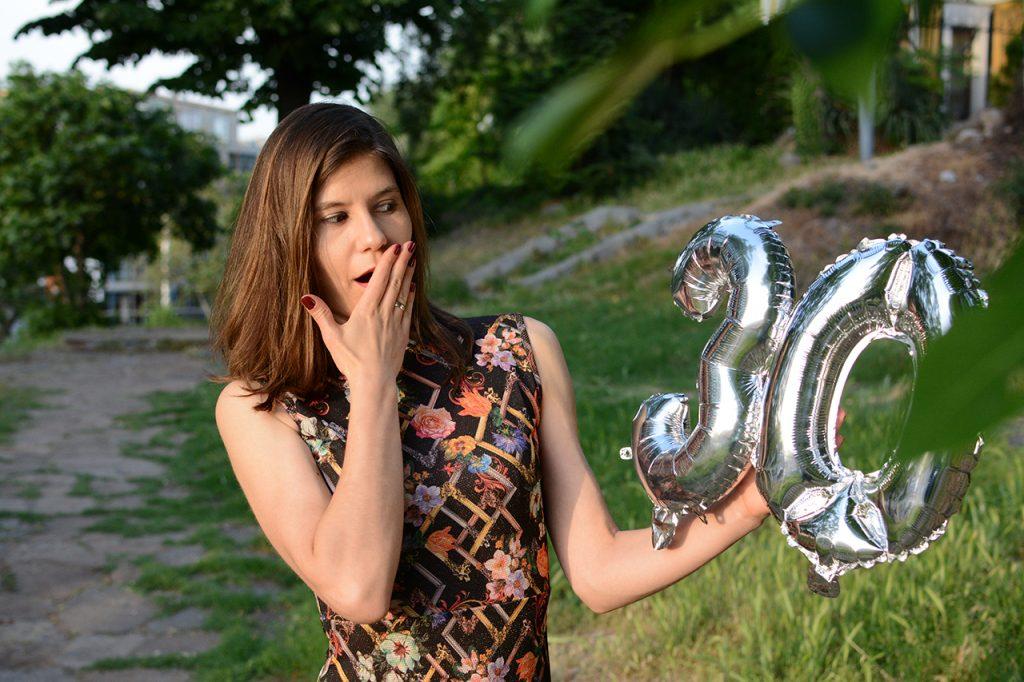 момиче държи балони с цифра 30