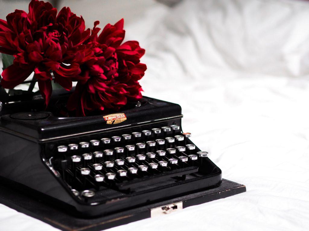черна пишеща машина и червени цветя на бял фон