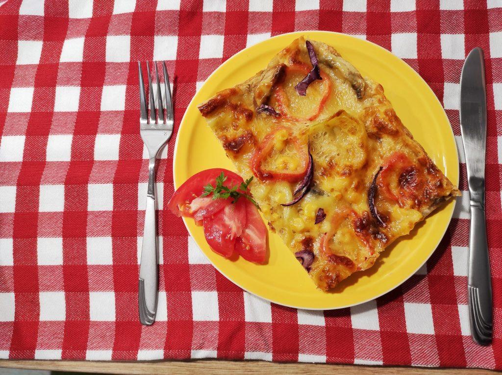 пица в жълта чиния на карирана покривка