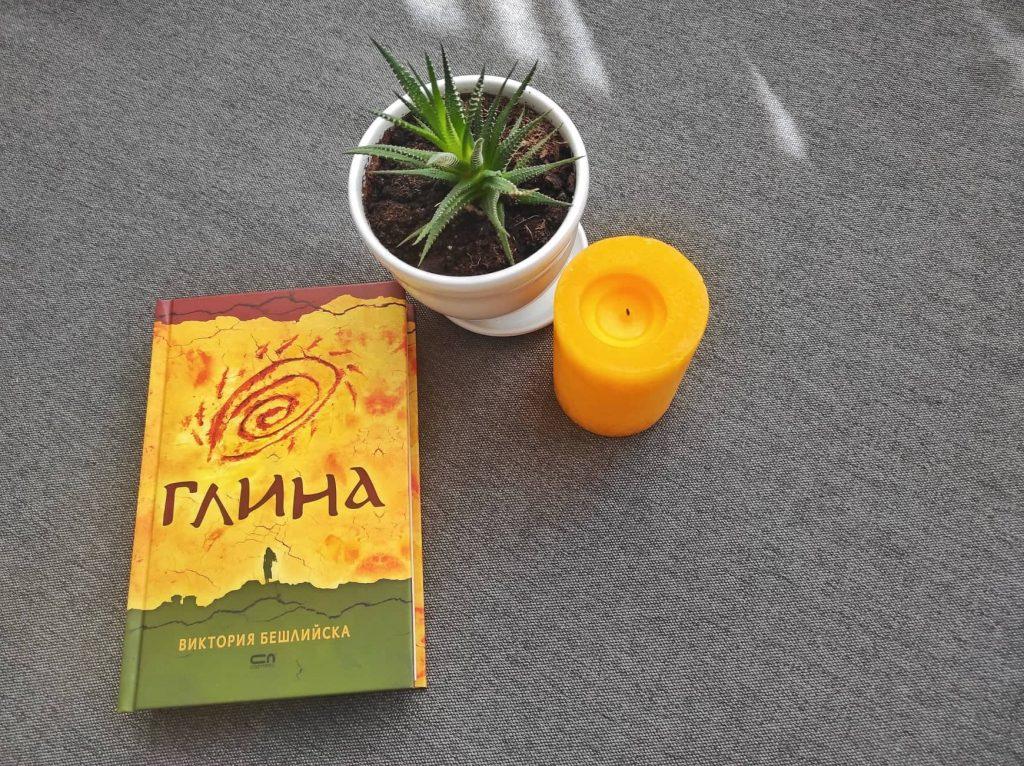 книгата Глина, свещ и саксия със зелено растение
