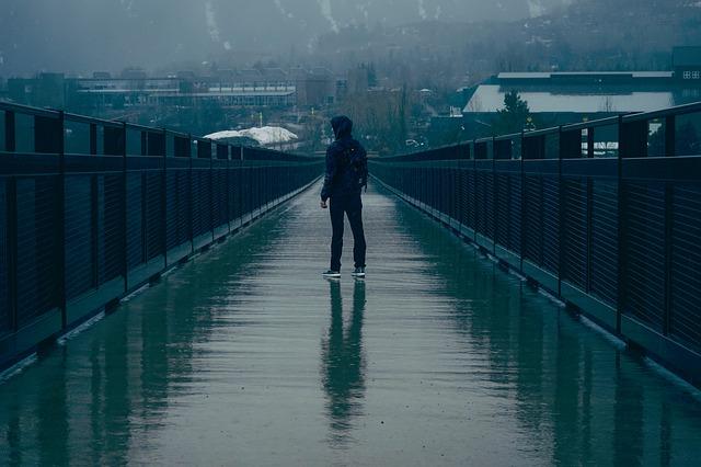 мъж на мост в дъждовно време